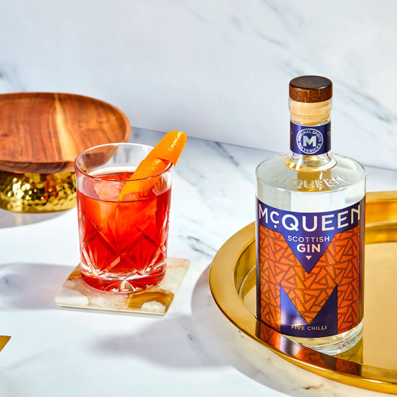A picture of a bottle of McQueen Five Chilli Scottish Gin and a Chilli Negroni cocktail
