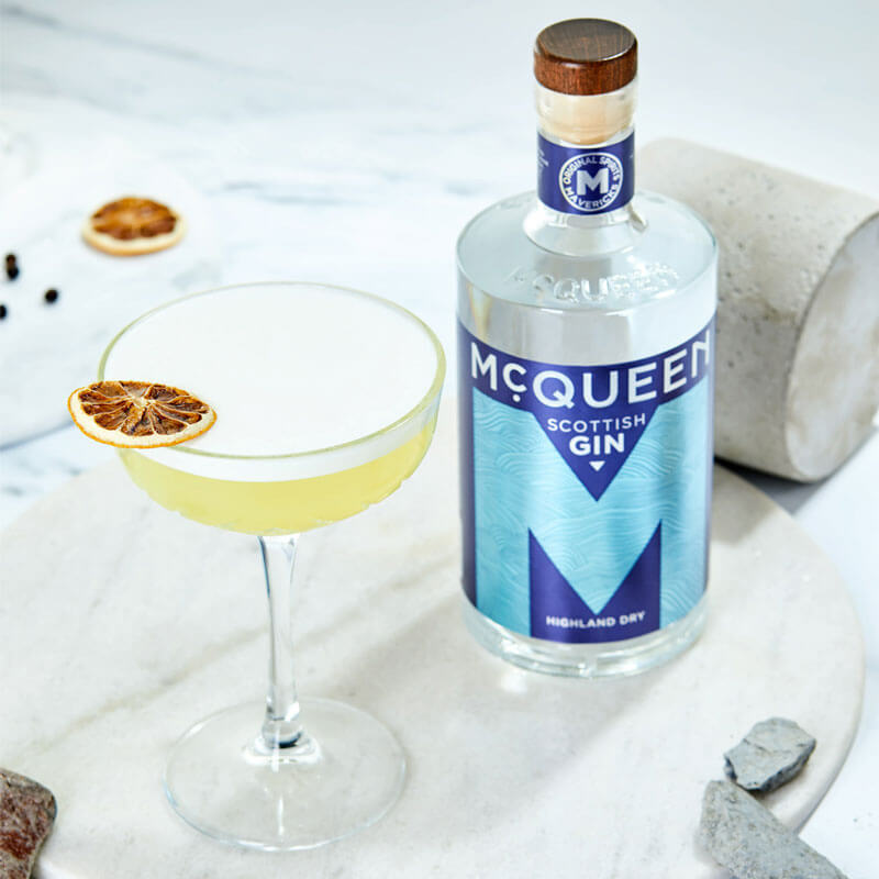 A picture of a bottle of McQueen Highland Dry Scottish Gin & a McQueen Bee's Knees cocktail