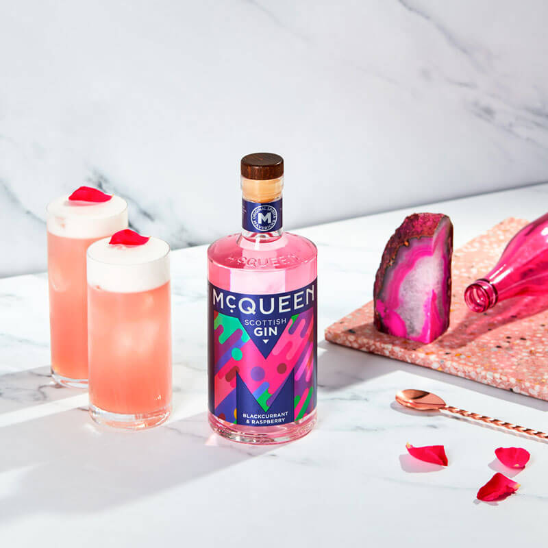 A picture of a bottle of McQueen Blackcurrant & Raspberry Scottish Gin & a Pink Fizz cocktail